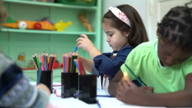 Preschool kids drawing in kindergarten classroom