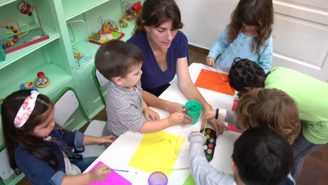 preschool kids painting with teacher at classroom - preschool stock videos and b-roll footage