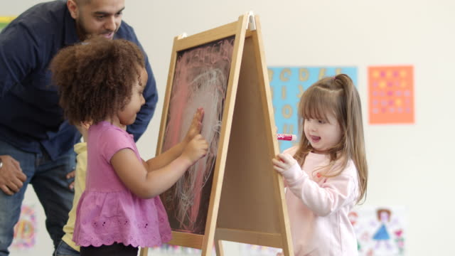preschool students draw on a chalk board in art class - chalk art equipment stock videos & royalty-free footage