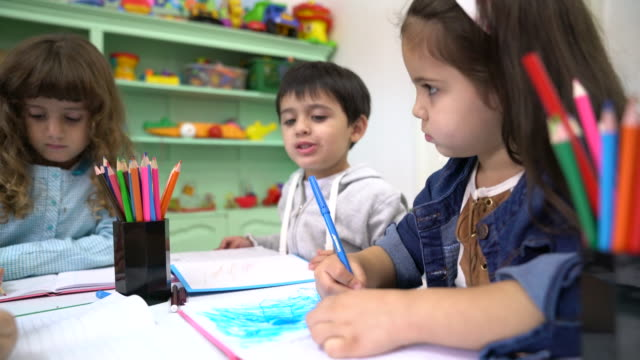 Preschool students drawing in books at classroom