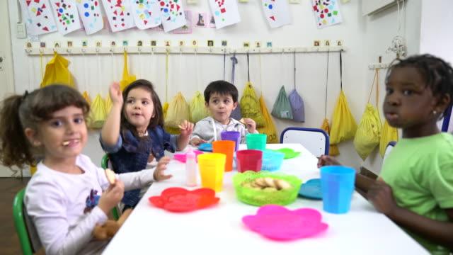 vídeos de stock e filmes b-roll de preschool students eating biscuits in classroom - merenda escolar