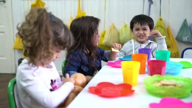 vídeos de stock, filmes e b-roll de estudantes de pré-escola comendo biscoitos em sala de aula - lanche