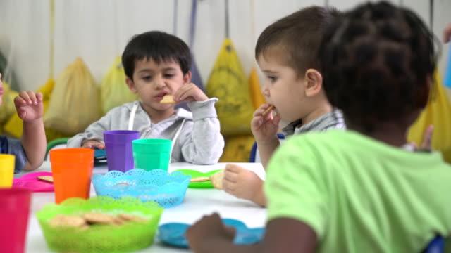 Preschool students eating snacks in classroom
