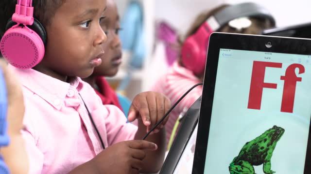 vídeos y material grabado en eventos de stock de pre-school students learning alphabet on digital tablet - niño pre escolar