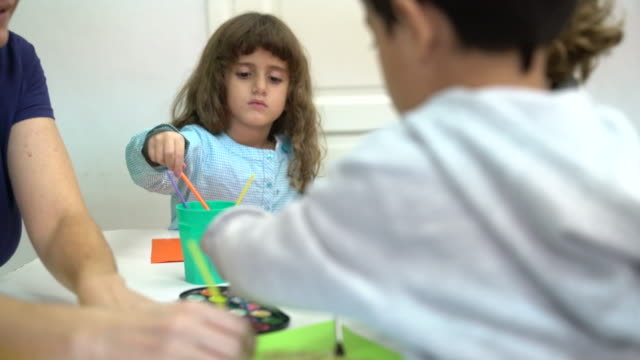 Preschool students painting with teacher at desk