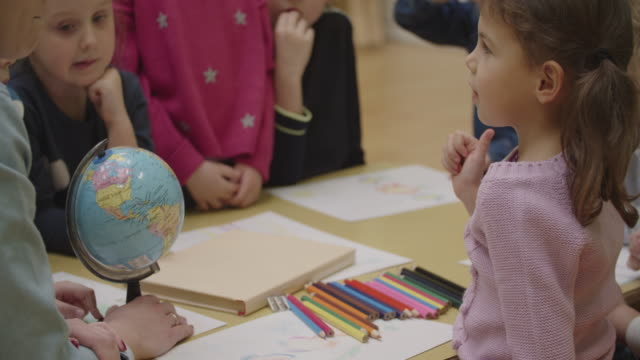 4k: preschool teacher and children learning geographic in classroom. - asking stock videos & royalty-free footage