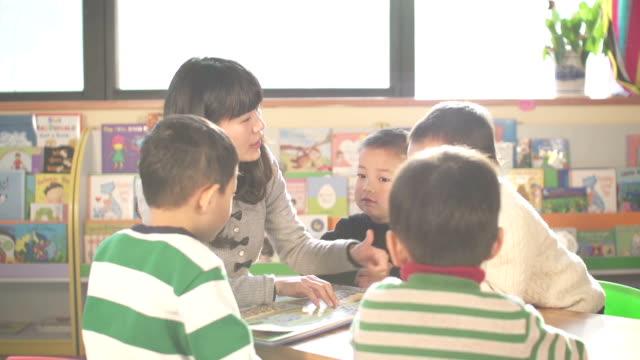 vídeos de stock e filmes b-roll de professor pré-escolar ensinando crianças em sala de aula - edifício de infantário