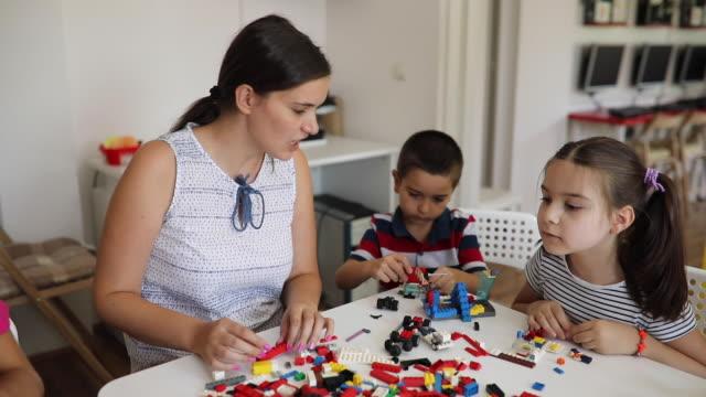 vorschullehrerin mit kindern mit kreativen aktivitäten - weibliche person stock-videos und b-roll-filmmaterial