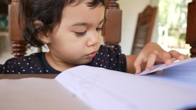 förskola thailändska etnicitet barn med penna för att öva skriva på en bok - endast flickor bildbanksvideor och videomaterial från bakom kulisserna