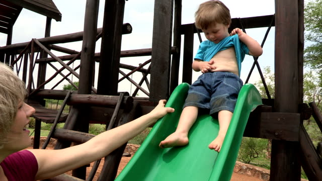 vidéos et rushes de pre-school toddler and mother playing on a slide in sandpit - 2 kid in a sandbox