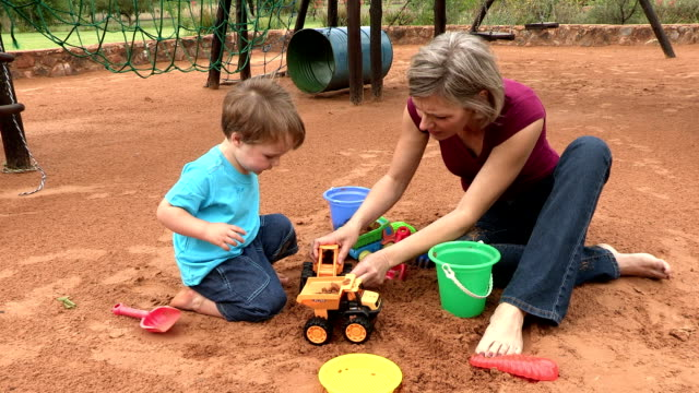 vidéos et rushes de pre-school toddler and mother playing with toys in a sandpit - 2 kid in a sandbox