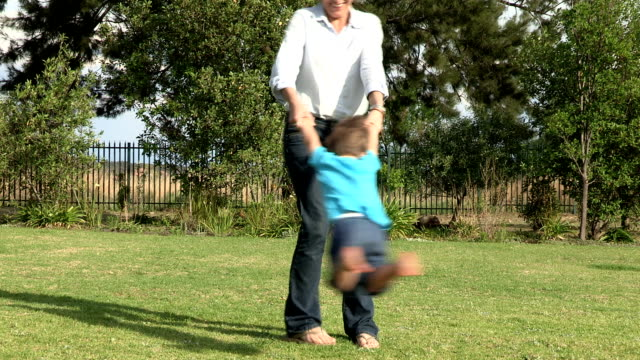 Pre-school toddler being swung in a circle on grass by mother