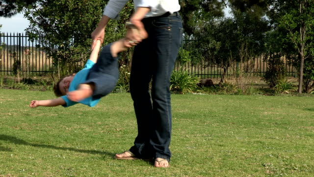 pre-school toddler being swung in a circle on grass by mother - going round in circles stock videos and b-roll footage
