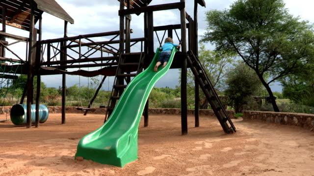 Pre-school toddler sliding down a slide