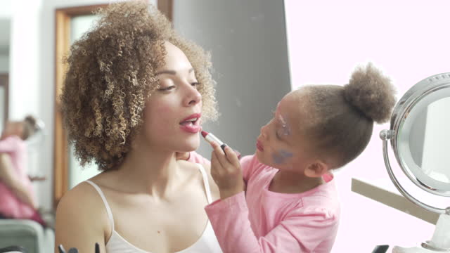 vidéos et rushes de preschooler putting make-up on mother - rouge à lèvres