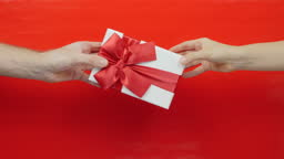 Present for St. Valentine's Day in hand on red background. Gift box with red ribbon bow for Birthday, Christmas or Valentines Day. Female hand gives present to male hand, close up