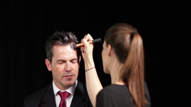 vídeos de stock, filmes e b-roll de tv presenter having make-up applied on set - aplicando