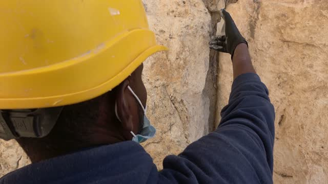 preservation worker injects a limestone-based liquid grout into fissures of the western wall's 2,000-year-old stones to preserve and reinforce them... - rosh hashanah stock videos & royalty-free footage