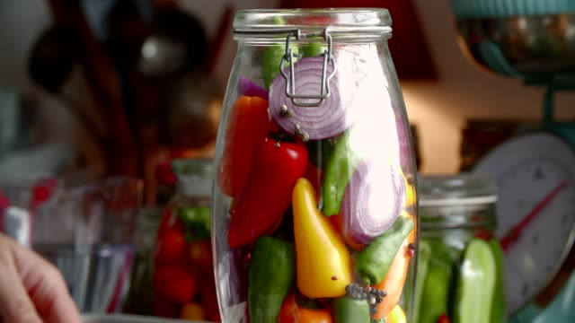 preserving organic colored red bell peppers in jars - peperone dolce video stock e b–roll