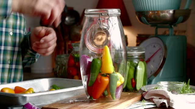 preserving organic colored red bell peppers in jars - preserved in oil stock videos and b-roll footage