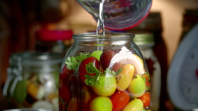 preserving organic mixed colored cherry tomatoes in jars - preserved in oil stock videos and b-roll footage