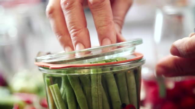 vídeos de stock, filmes e b-roll de preservação de vegetais orgânicos em frascos - conserva