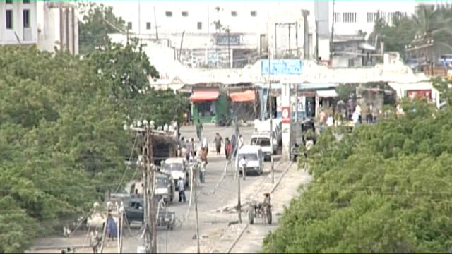 President and Prime Minister attempt to consolidate power / Violence in Mogadishu High angle view people and vehicles on street