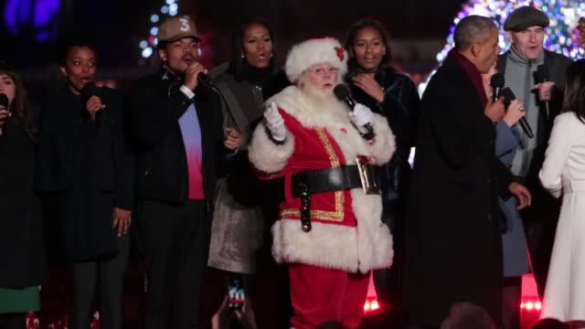 President Barack Obama and the first family join the featured performers onstage at the end of the 94th Annual National Christmas Tree Lighting...