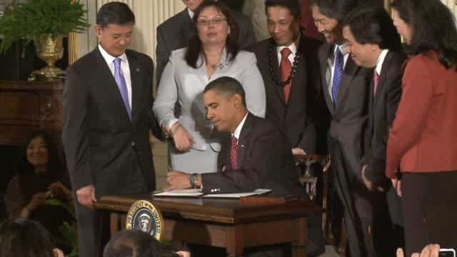 vídeos de stock e filmes b-roll de s president barack obama signing an executive order on asian american and pacific islanders initiative with commerce secretary gary locke on october... - sentar se