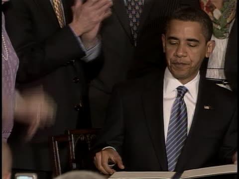 president barack obama signs a bill into law as observers applaud. - disegno di legge video stock e b–roll