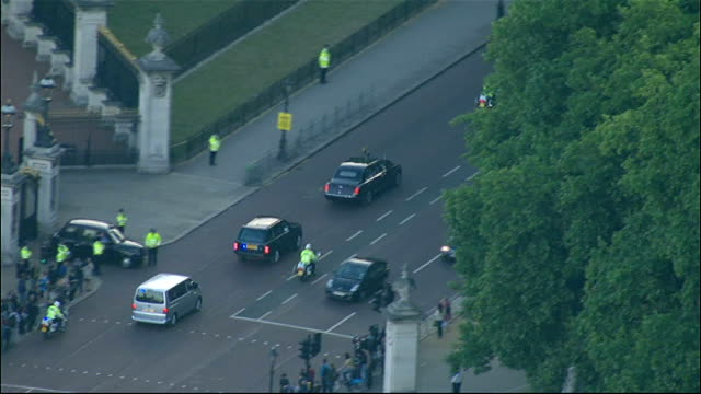 day 2 aerials of queen leaving buckingham palace for winfield house england london of motorcade departing buckingham palace for winfield house / pull... - motorcade stock videos & royalty-free footage