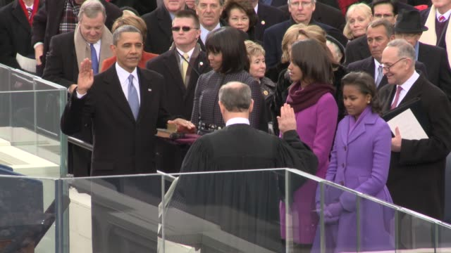 vídeos de stock e filmes b-roll de / president barack obama takes the oath of office and is sworn in by chief justic john roberts us presidential election 2013 at us capitol steps on... - 2013