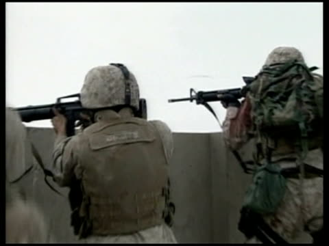 stockvideo's en b-roll-footage met president bush likens iraq war to vietnam 2004 fallujah ext american troops on rooftop firing weapons during battle american troops running through... - al fallujah