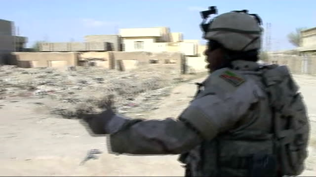 president bush warns that troop withdrawal would have 'devastating' consequences; iraq: ramadi: ext iraqi troops climb up into truck as chant a... - イラク点の映像素材/bロール