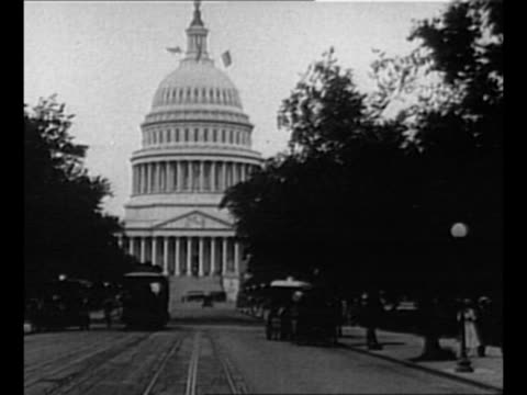 us president calvin coolidge and wife grace exit former president woodrow wilson's home / ws us capitol at end of street with trolley cars in... - 1910 1919 stock-videos und b-roll-filmmaterial