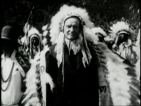 US President Calvin Coolidge wears a Native American Headdress while visiting with American Indians in 1920