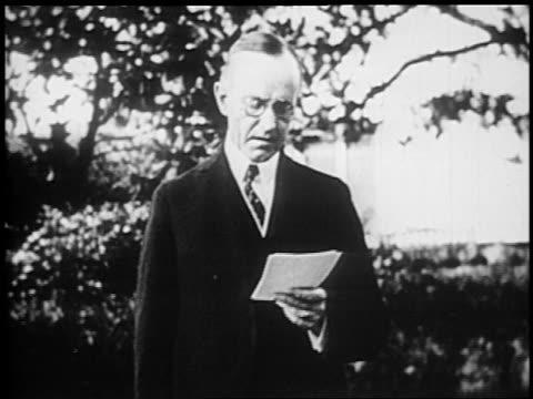 vidéos et rushes de president calvin coolidge with eyeglasses reading speech outdoors during re-election campaign - 1924