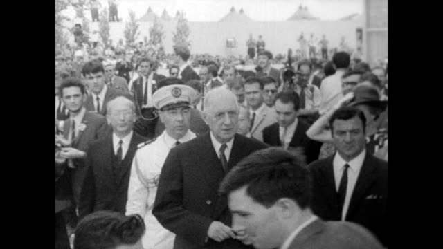 / president charles de gaulle walks before crowd at the 1967 expo in montreal / flags of the nations flutter / de gaulle visits the exhibits at the... - charles de gaulle stock videos & royalty-free footage