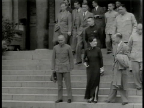President Chiang Kaishek down steps w/ wife Madame Soong Mayling Chinese English officers MS Kaishek Mayling standing CU Kaishek nodding MS Soldiers...