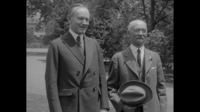 president coolidge and retiring postman bernhard jedding of battle creek mi stand together outdoors smiling jedding puts on his hat and poses for a... - coolidge calvin stock videos & royalty-free footage