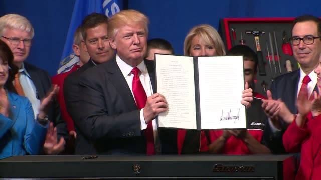 "president donald trump signed an executive order--directing federal agencies to implement the ""buy american, hire american"" rhetoric of his... - 署名点の映像素材/bロール"