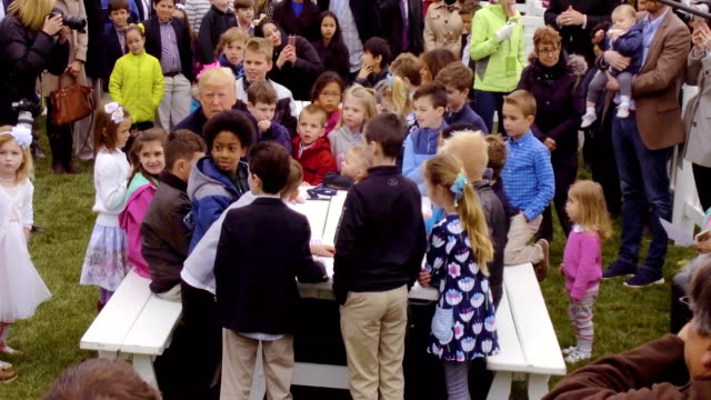 us president donald trump sits with children as they write messages to military troops during the 140th annual easter egg roll on the south lawn of... - vanessa haydon stock-videos und b-roll-filmmaterial