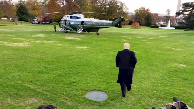 US President Donald Trump speaks to members of the media shakes hands with people and boards the Marine One for his departure from the South Lawn of...