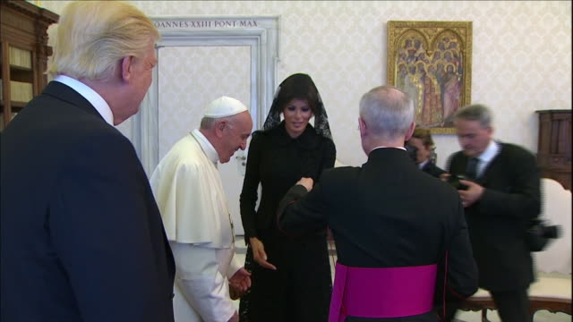 cu president donald trump stands and smiles as first lady melania trump shakes hands with pope francis at vatican city cameras flash and papal staff... - religion or spirituality bildbanksvideor och videomaterial från bakom kulisserna
