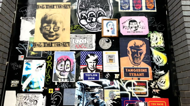 us president donald trump's image is used in satirical posters and graffiti on a wall on august 23 2018 in london england - poster stock videos & royalty-free footage