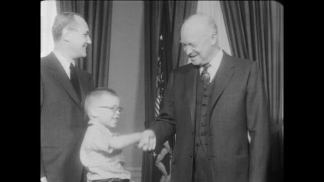 president dwight eisenhower in oval office standing holding young girl in his arms / girl attaches paper poppy for vfw poppy buddy campaign to ike's... - veterans of foreign wars of the united states stock videos & royalty-free footage