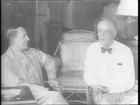 President Franklin D Roosevelt and his War Council confer in a room with a map of the Pacific / General MacArthur with pointer points on the map /...