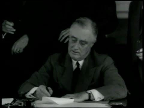 President Franklin D Roosevelt signing paper on his desk