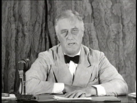 president franklin d. roosevelt sits at a desk and makes a speech about social security. - 社会保障点の映像素材/bロール