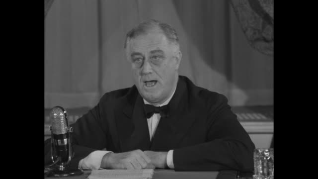 vídeos y material grabado en eventos de stock de president franklin d roosevelt sitting at desk speaking into microphone re promoting aid to us allies to fight against axis threat throughout world... - franklin roosevelt